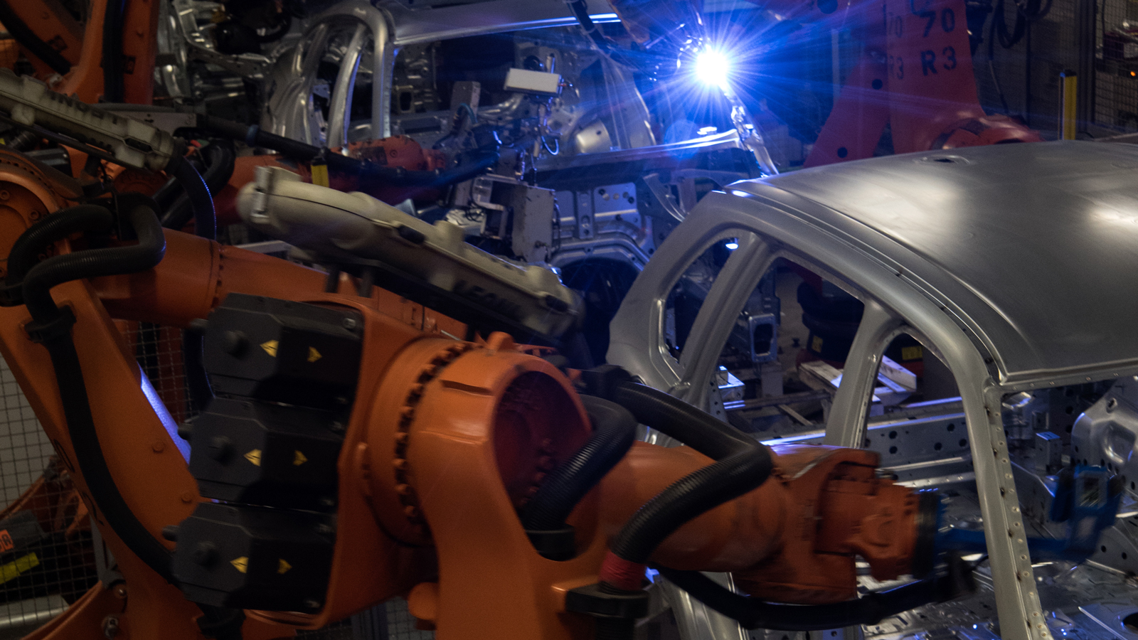 Robot welding in the body shop occurs in large cages to protect workers, who monitor the robots from afar. (4 of 7)