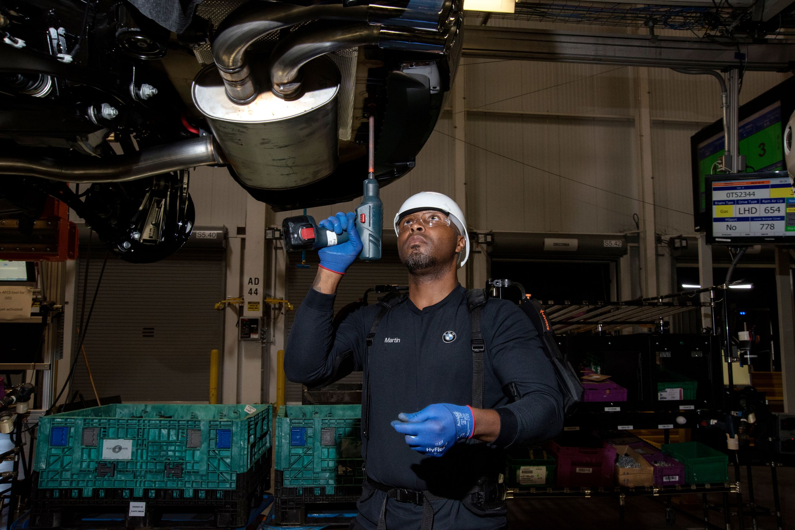 Assembly line worker Lee Martin fastens screws to the underbody of a car using an ergonomic arm support to reduce the strain of long periods working with his arms raised. (6 of 7)