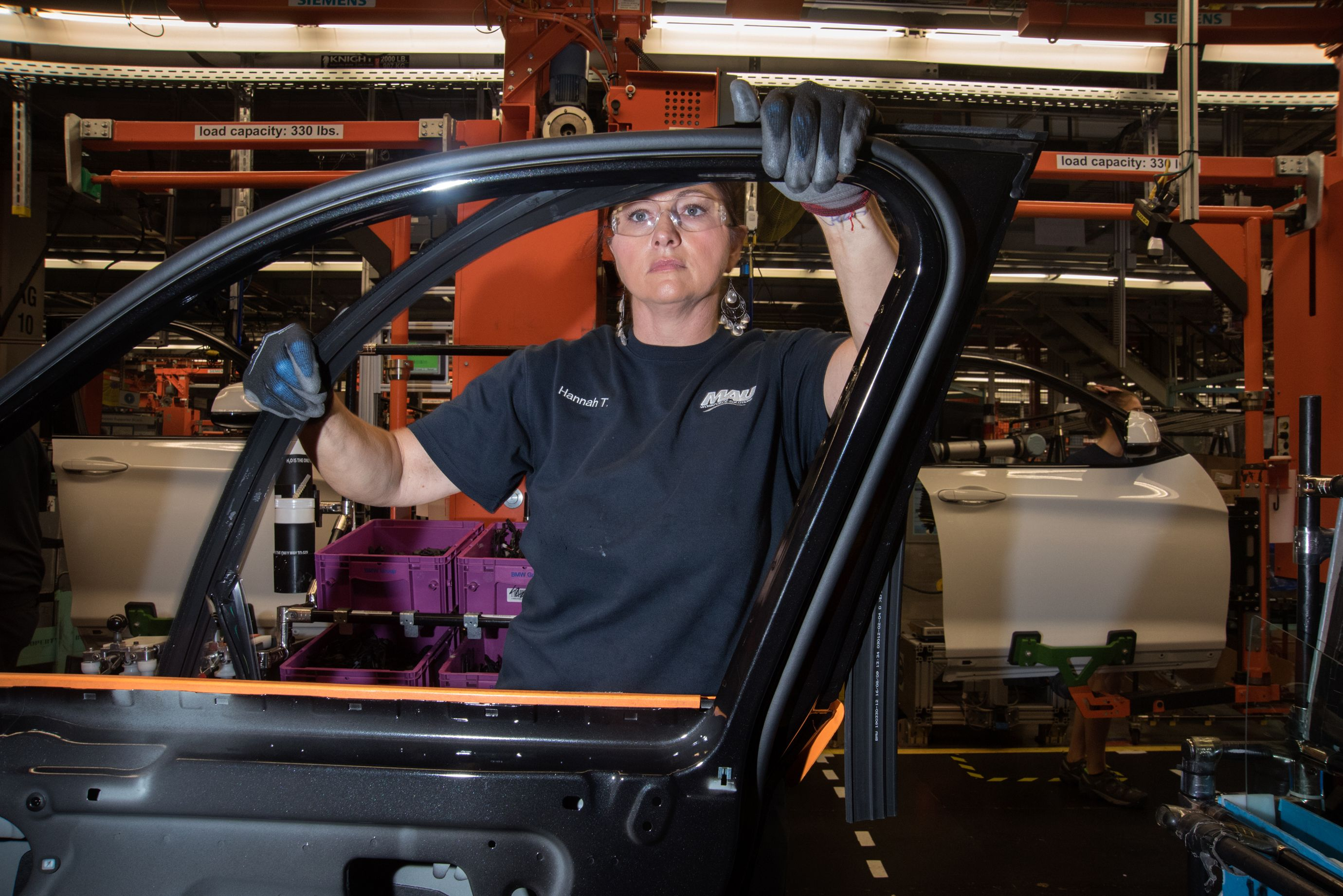 An employee of MAU, a firm that provides contract workers to BMW, helps to assemble a door. (5 of 7)