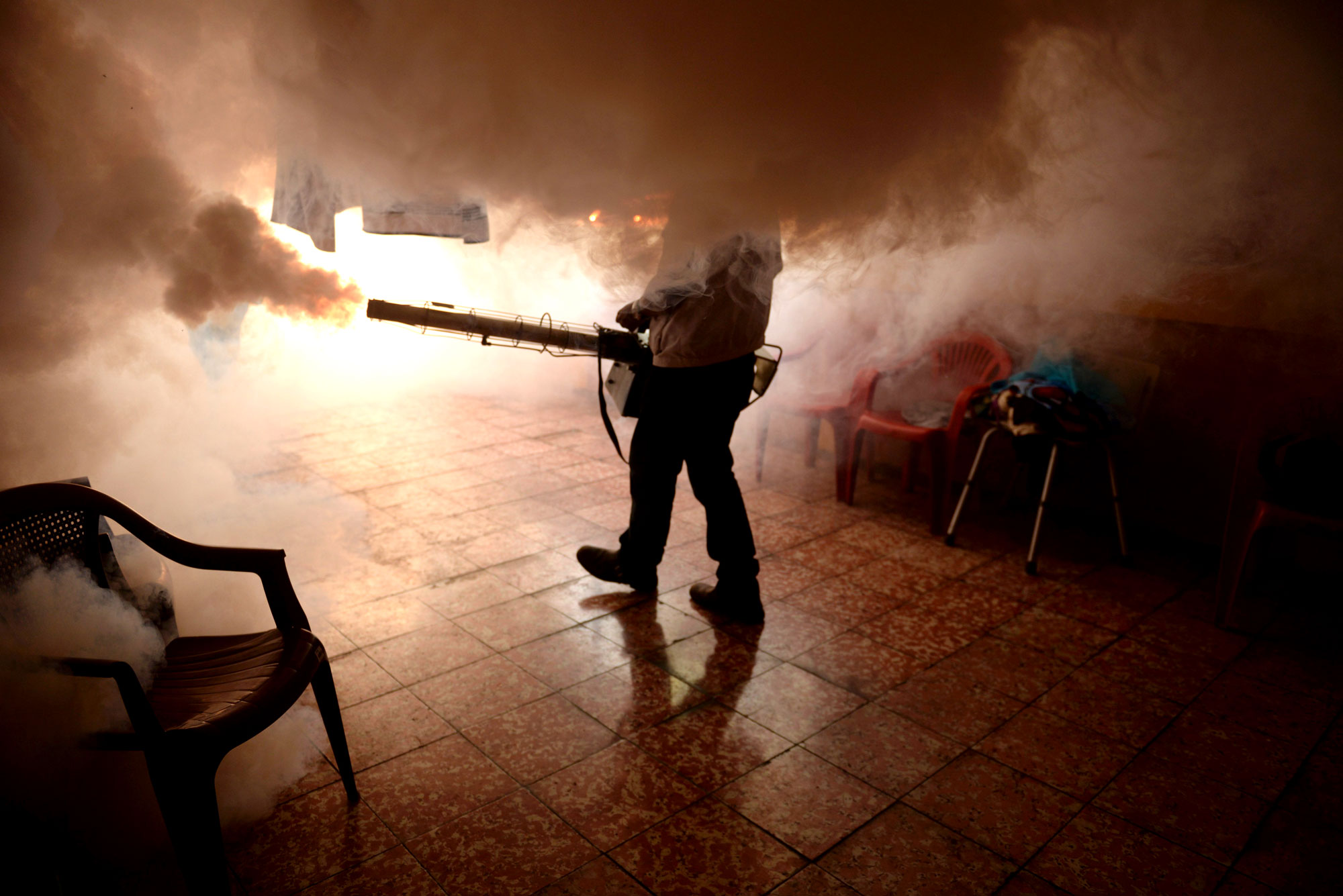 A health worker fumigates a home in El Salvador against mosquitoes to prevent the spread of the Zika virus.