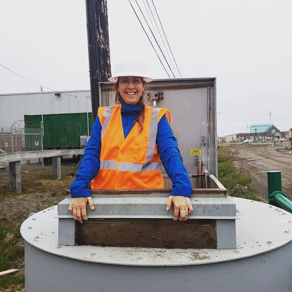 O'Connor standing in the entrance to a utility tunnel in Utqiagvik, Alaska.